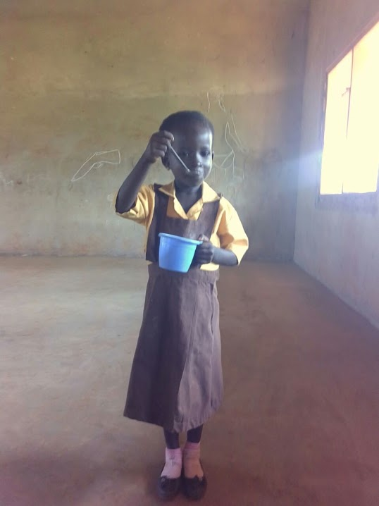 young girl stands eating porridge