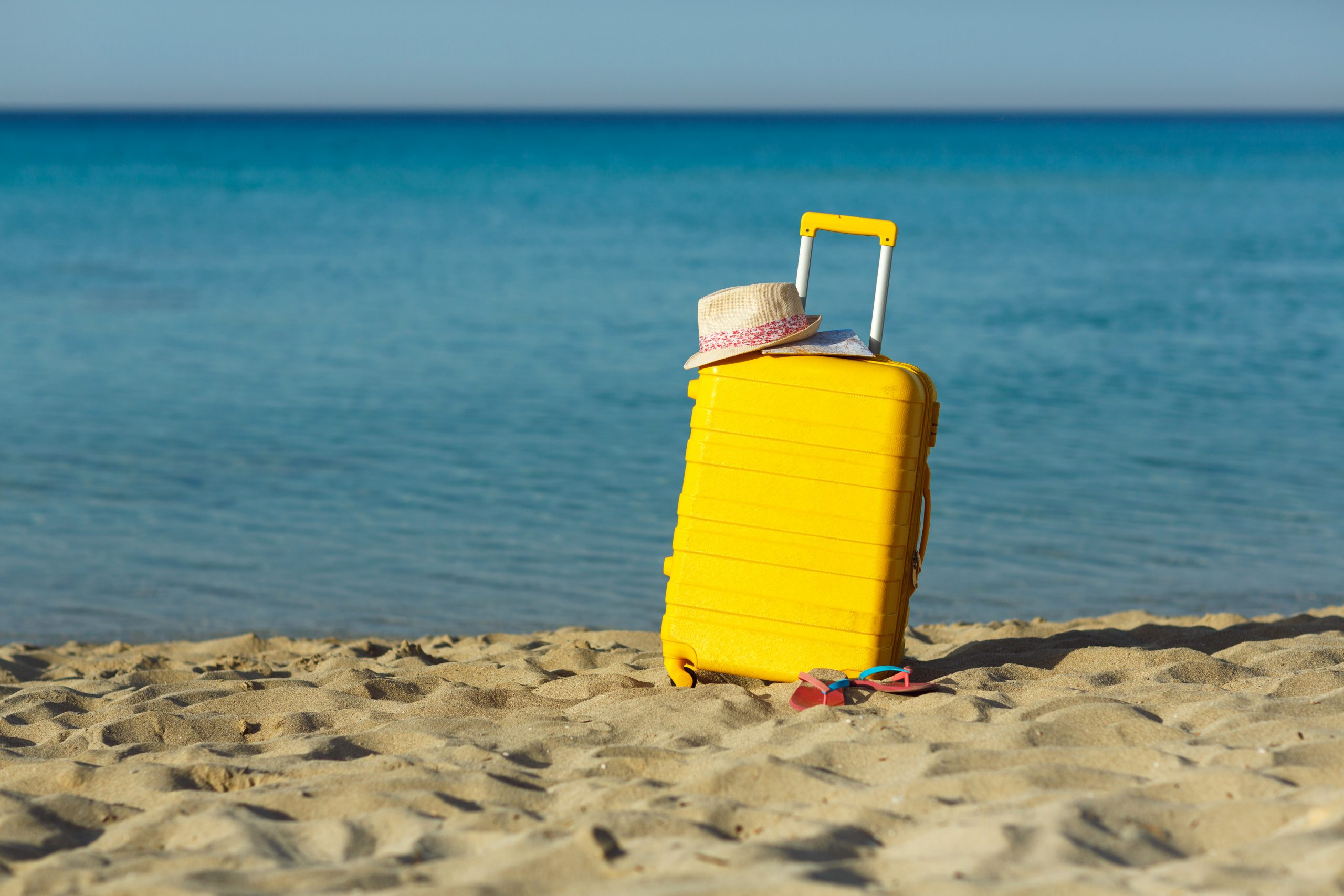 Travel holiday vacation yellow suitcase with map, straw hat and beach slippers on the beautiful sand beach on SelfishMe Travel