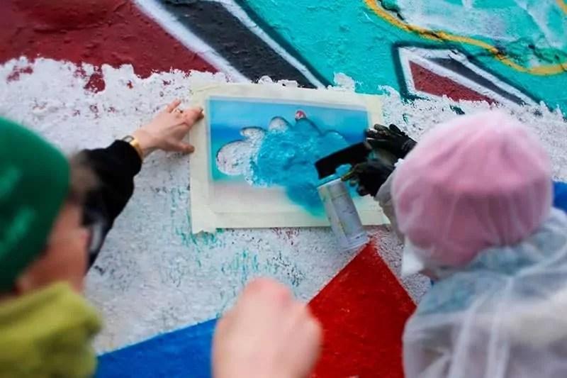 Schüler sprühen ein Schablonen Graffiti- Ein Workshop mit Ostap