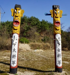 Jangseung, Korean totems or devil-poles, are supposed to ward off evil spirits. Variations on these guys are at the edge of villages throughout Korea. They have a dried fish tied round their necks for good measure.