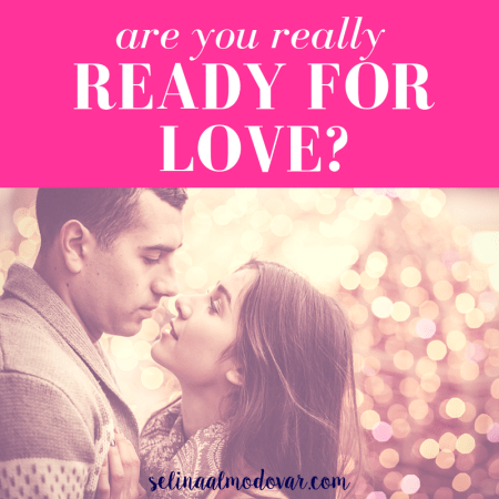 "girl looks up at guy as they hold each other with bright Christmas lights in the background with pink overlay and white text that reads, ""Are You Really Ready for Love?"""