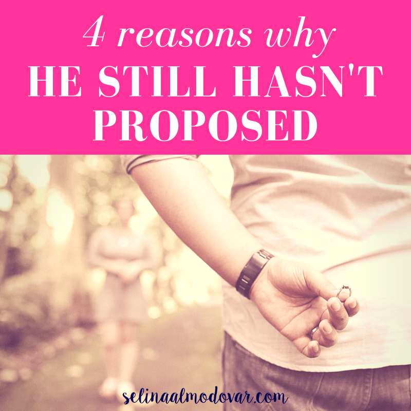 "man holding ring behind his back while facing a woman who stands in the distance with pink overlay and white text that reads, ""4 Reasons Why He Still Hasn't Proposed"""