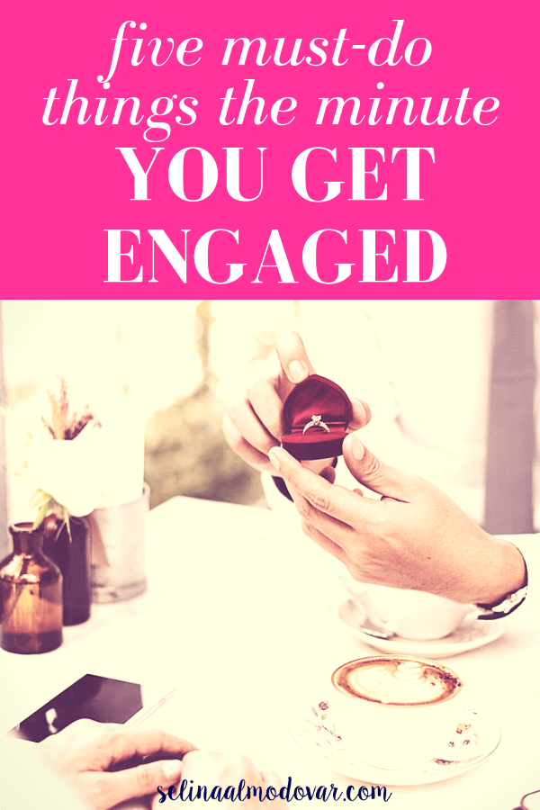"hands of a man holding a red velvet that contains a diamond while sitting across from a woman at a restaurant dinner table with pink overlay and white text that reads, ""Five Must-Do Things the Minute You Get Engaged"""