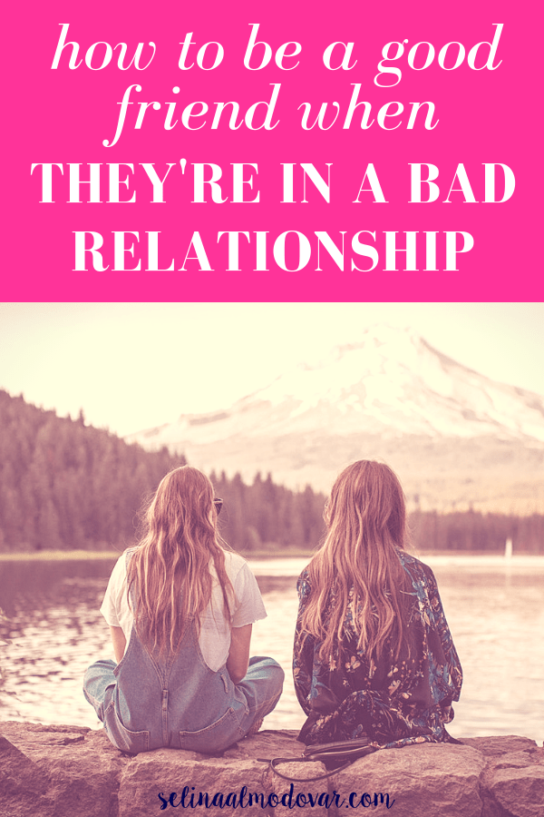 "back view of two girls sitting on stone wall looking at a mountain view with pink overlay and white text that reads, ""How to Be a Good Friend When They're In A Bad Relationship"""