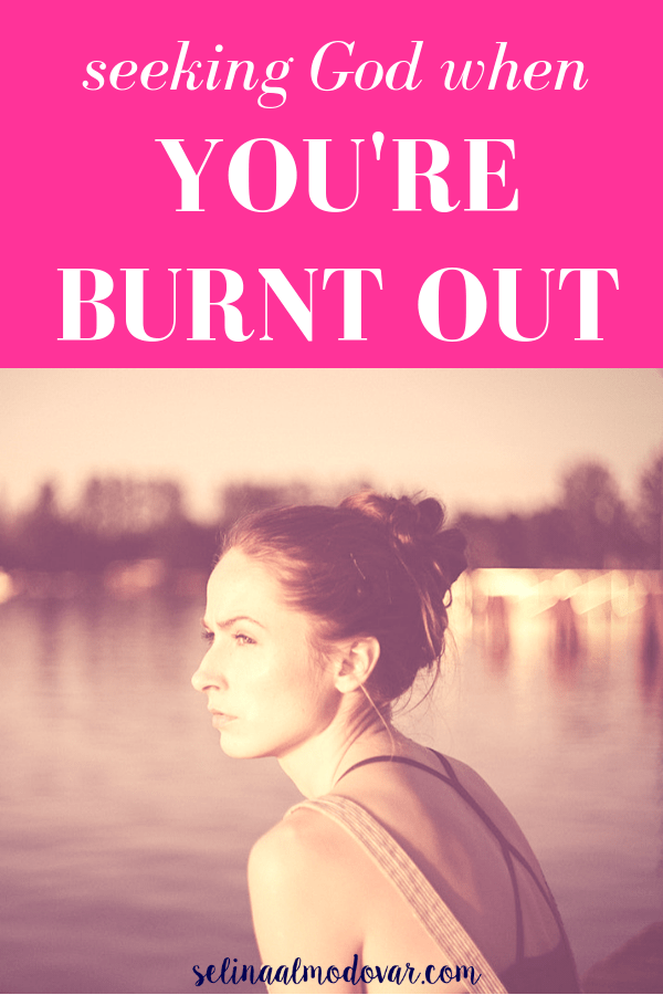 "girl looking stressed with messy top bun stares out over lake view during sunset hours with pink overlay and white text that reads, ""Seeking God When You're Burnt Out"""