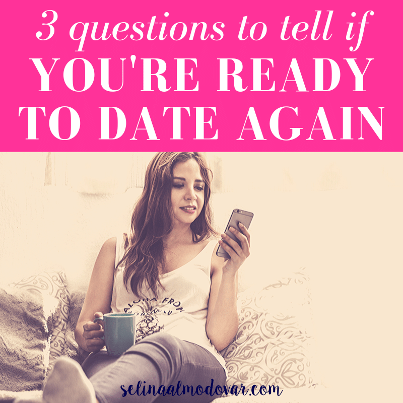 "girl sitting on her bed holding a cup of coffee smiles as she stares at her phone with pink overlay and white text that reads, ""3 Questions To Tell If You're Ready To Date Again"