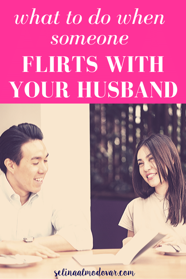 "guy sits at table with girl looking at open book while girl smiles and looks at him with pink overlay and white text that reads, ""What To Do When Someone Flirts With Your Husband"""