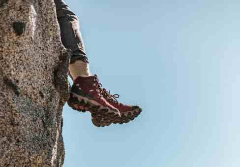 Dangling feet over a cliff in hiking boots