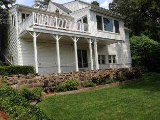 View of back of home with stately columns and manicured yard