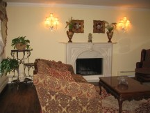 Formal Living Room with wood burning fireplace, Schonbeck sconces, new custom stained hardwood flooring.