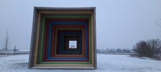 Die Seh-Station fokussiert im leichten Schnee über dem grünen Gras den Blick auf die leicht beschneite Lichtkuppel auf dem Rodelhügel