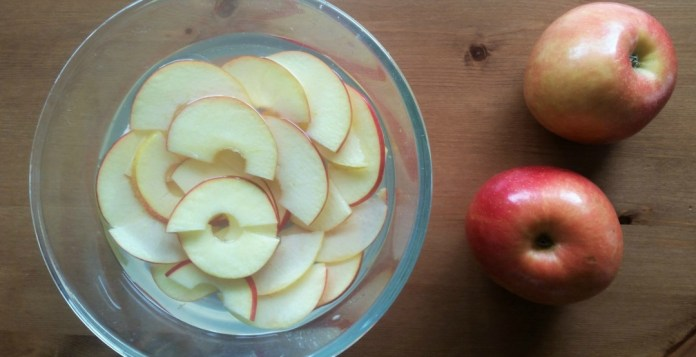 Manzana laminada en un bol con agua y limón