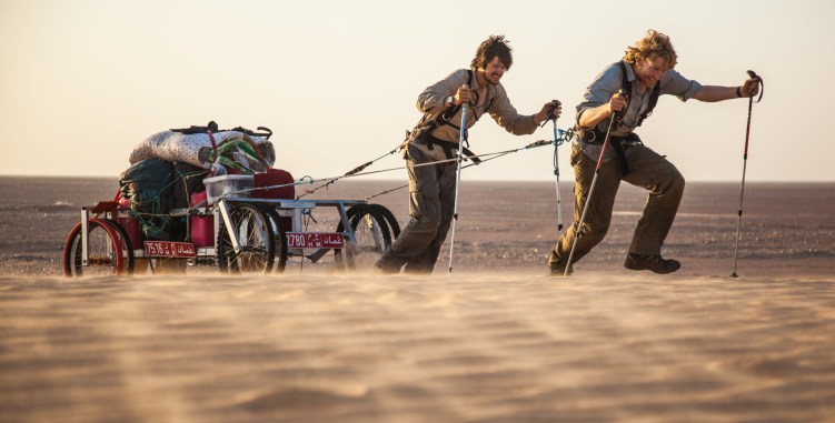 "Alastair Humphreys and Leon McCarron walk with their supply cart in the film ""Into the Empty Quarter"""