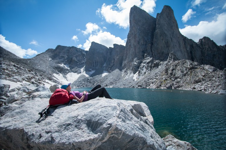 Hilary Oliver rests in the sun at Donna Lake, looking up at Pronghorn Peak in Wyoming's Wind River Range