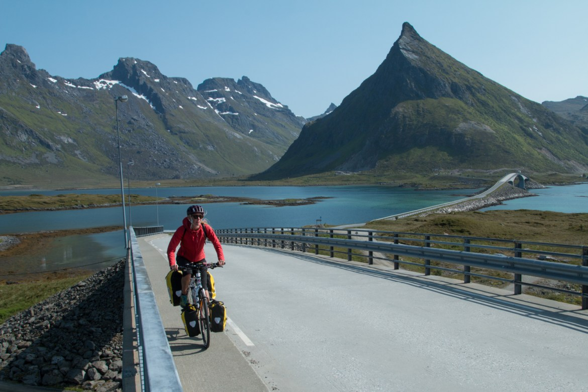 Hilary Oliver rides a fully loaded touring bike across the bridges to Fredvang, Norway, on the way to Kvalvika.