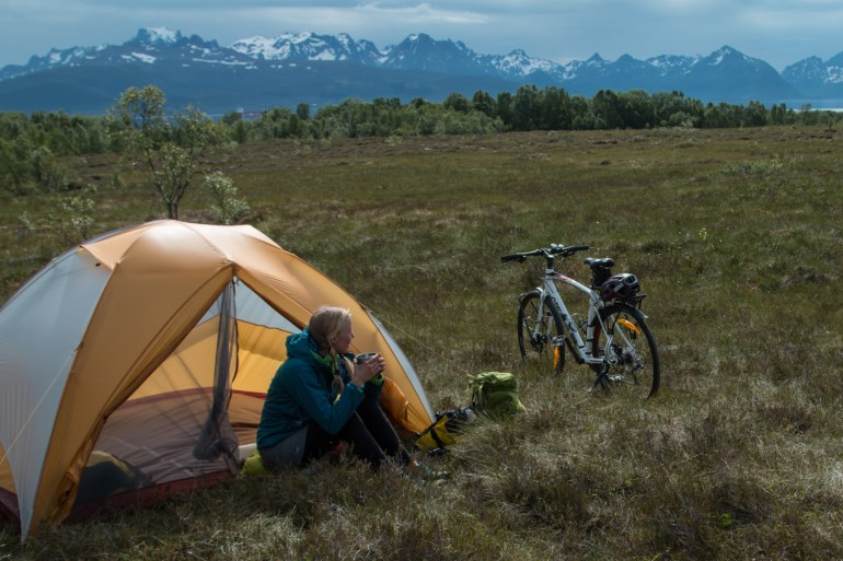 Hilary Oliver sips morning coffee in camp during a bike tour through Norway's northern islands.