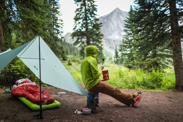 forest woodward photo of backpacker eating dinner at campsite
