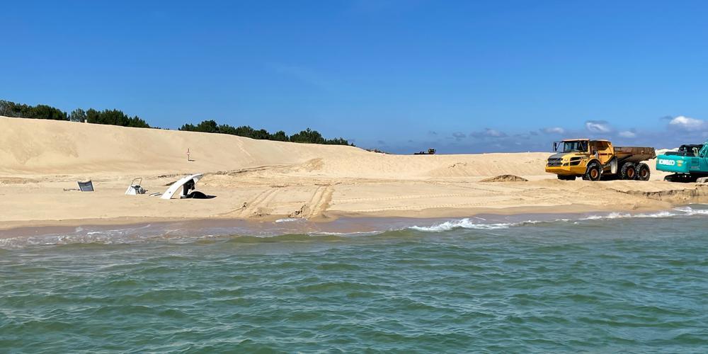 Le bateau ensablé se trouve à 60 mètres de la digue de Benoît Bartherotte dont les pelleteuses témoignent de la lutte contre l'érosion. © Crédit photo : Thiéry Nadé