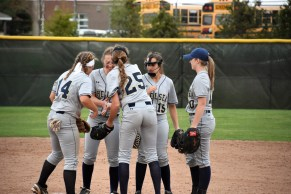 Pitcher Peighton Root gatherswith her infielders after a big strikeout
