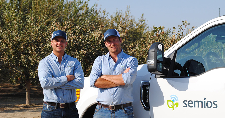Members of the Semios Field Services Team standing in an orchard