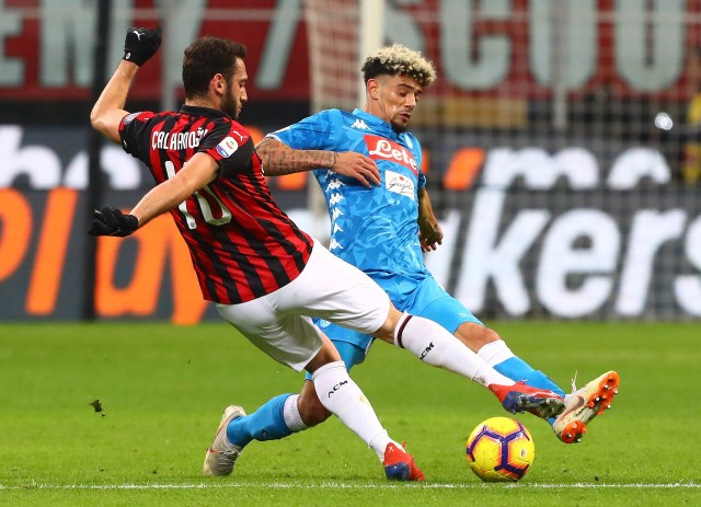 MILAN, ITALY - JANUARY 26: Hakan Calhanoglu of AC Milan is challenged by Kevin Malcuit (back) of SSC Napoli during the Serie A match between AC Milan and SSC Napoli at Stadio Giuseppe Meazza on January 26, 2019 in Milan, Italy. (Photo by Marco Luzzani/Getty Images)