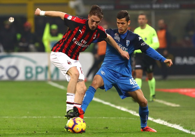 MILAN, ITALY - FEBRUARY 22: Salih Ucan (R) of Empoli competes for the ball with Andrea Conti (L) of AC Milan during the Serie A match between AC Milan and Empoli at Stadio Giuseppe Meazza on February 22, 2019 in Milan, Italy. (Photo by Marco Luzzani/Getty Images)