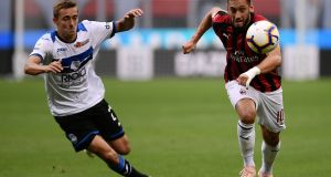 Atalanta's Belgian defender Timothy Castagne (L) and AC Milan's Turkish midfielder Hakan Calhanoglu rush to the ball during the Italian Serie A football match between AC Milan and Atalanta Bergamo on September 23, 2018 at the San Siro Stadium in Milan. (Photo by MARCO BERTORELLO / AFP) (Photo credit should read MARCO BERTORELLO/AFP/Getty Images)