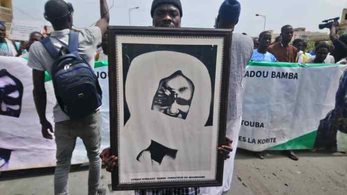 - Un groupe de personnes regardant un homme faisant un tour sur une planche à roulettes - Amadou Bamba