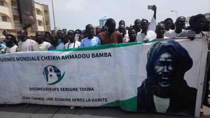 - Un groupe de personnes debout devant une foule - Amadou Bamba