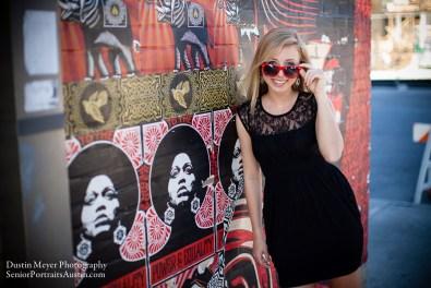 Blonde female teen model senior portraits black dress sunglasses graffiti wall South Congress