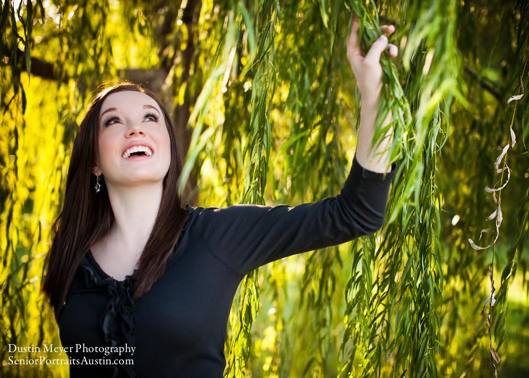 Brunette teen female model senior portraits laugh smile black long sleeve shirt willow tree green leaves photo