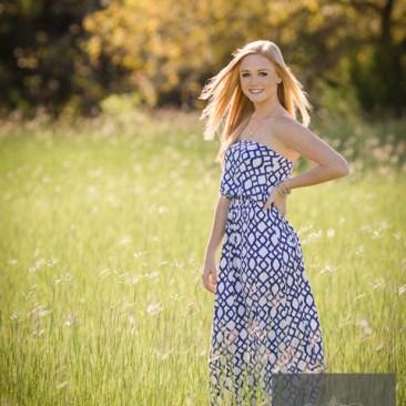 Senior portraits photography photos blonde Blue eyes sun flare sunshine outdoors tall grass field high fashion photography