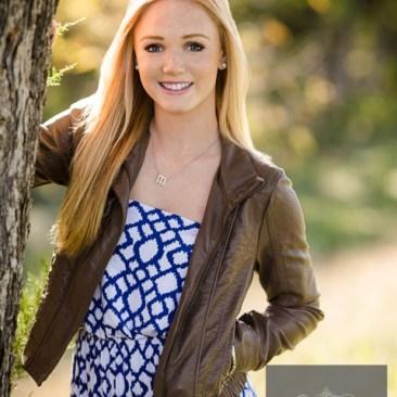 High school senior portraits one female Blue dress brown jacket tree outdoors sunshine smile