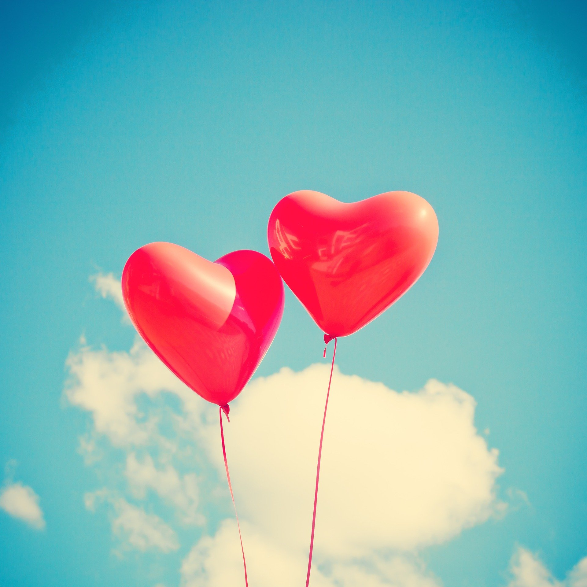 red heart shaped balloons against a blue sky