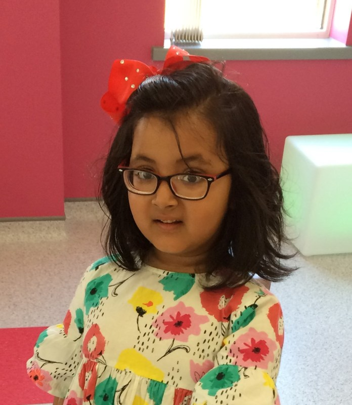 A young girl who has Bardet-Biedl syndrome. She has black hair and a pink bow in her hair