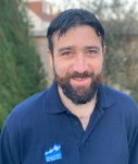 A photo of Jan Brent. He has short dark hair and a beard and is wearing a blue polo shirt