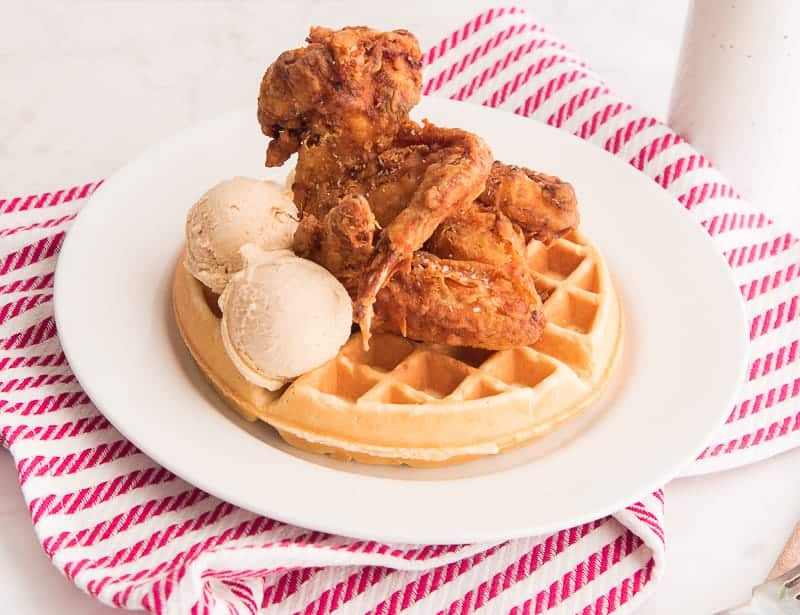 A white plate over a red and white striped towel on the plate are Chicken and Waffles with two scoops of Maple-Cinnamon Butter