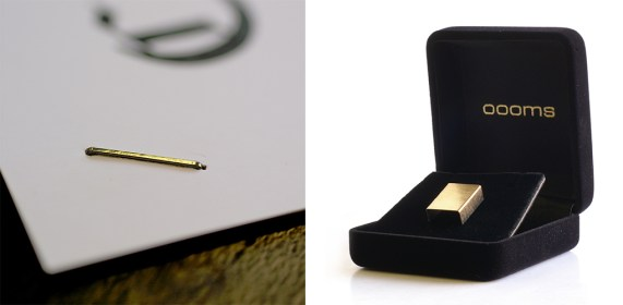 Gold Staples In An Elegant Black Box, With One Staple Shown In The Corn Of A Piece Of Paper