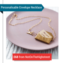 A Gold Envelope Necklace On A Pink Plate With The Text 'Personalisable Envelope Necklace £68 From NotOnTheHighstreet'
