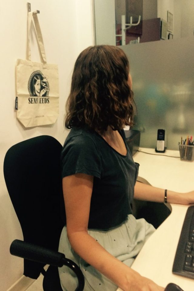 Photo of the patient Covadonga F., seen in profile and sitting in front of a table in an office.  Behind her is a Sensi Seeds bag hanging from a hook.