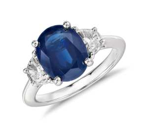Blue Nile Oval Sapphire and Diamond Ring in Platinum (10x8mm) Distinctly glamorous, this sapphire and diamond ring showcases a deep blue, oval sapphire with two half-moon diamond side stones. This platinum three-stone ring is a beautiful diamond engagement ring option.