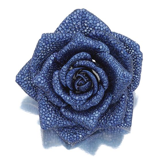 SAPPHIRE BROOCH, 'LA ROSE DE BOURBON', MICHELE DELLA VALLE Designed as a rose, set with circular-cut sapphires, mounted in white gold and titanium