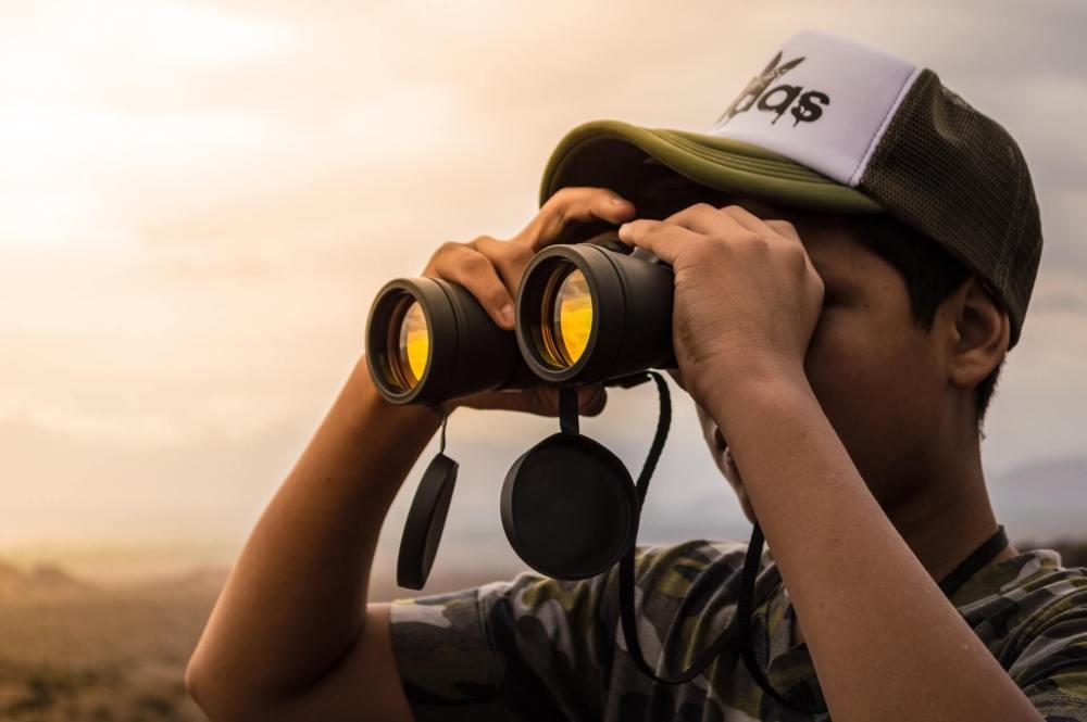 boy searching through binoculars