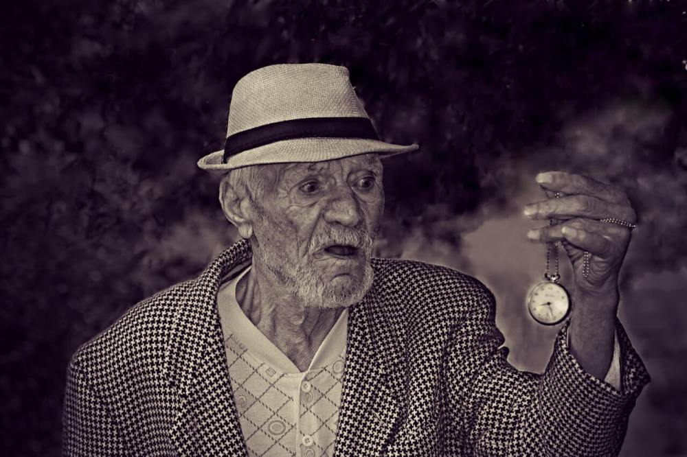 elderly gentleman holding a pocket watch