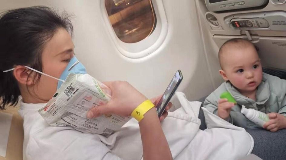 Une femme et un bambin à leurs sièges dans un avion.