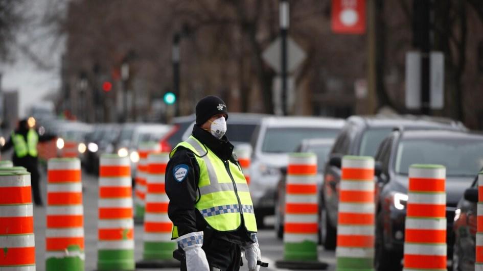 Un policier portant un masque surveille les automobilistes qui attendent en file pour se rendre à la clinique de dépistage.