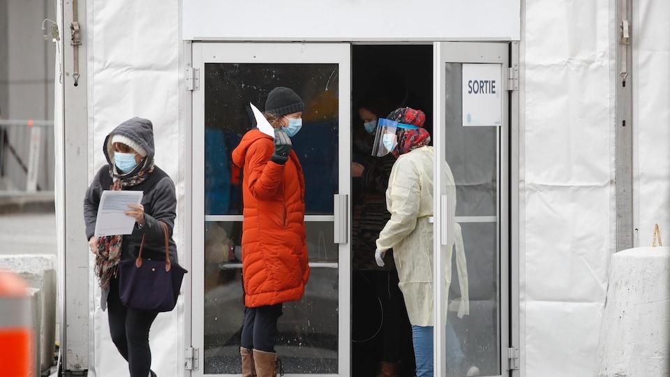 Une travailleuse de la santé discute avec une femme à la sortie de la clinique de dépistage.