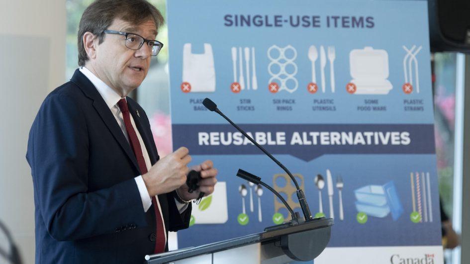 Jonathan Wilkinson, en conférence de presse. À ses côtés, une affiche illustre quels produits peuvent remplacer ceux qui seront bannis.