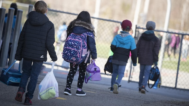Des enfants gardent une bonne distance entre eux avant d'entrer dans une cour d'école.