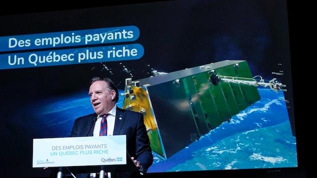 François Legault au micro avec, en arrière-plan l'image d'un satellite dans l'espace